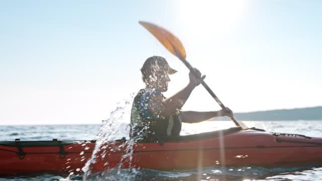vidéos et rushes de slo mo homme pagayant à travers la mer dans son kayak de mer sur une journée ensoleillée - kayak