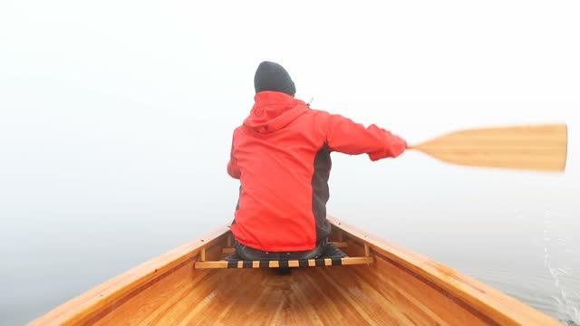 Man paddling canoe on the foggy lake