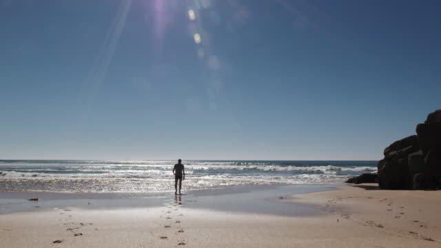 Man paddling in the sea at Pedn Vounder Beach, Cornwall on a bright sunny day. video