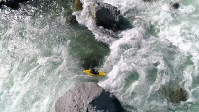 Man Paddling Kayak in Raging Whitewater Aerial Drone flying above kayaker charging fast into waves of river rapids rapids river stock videos & royalty-free footage