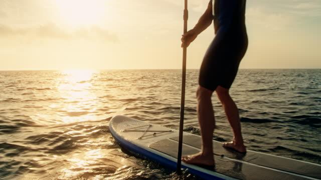 stockvideo's en b-roll-footage met man peddelen op zijn sup bij zonsondergang - paddle
