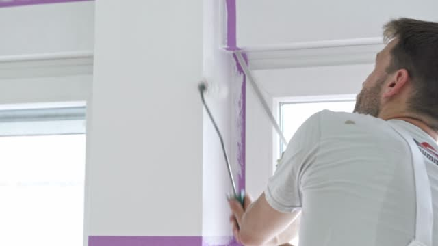 Man painting a wall with small painting roller