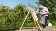 istock Man painting at the Lake shore 1272643006