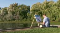 istock Man painting at the Lake shore 1272664286
