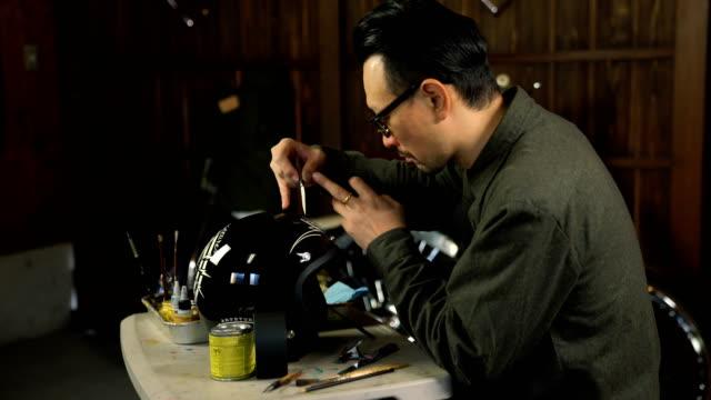 Man painting custom artwork onto a motorcycle helmet video