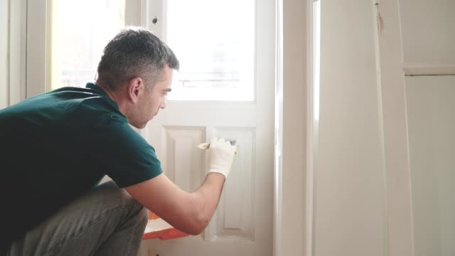 Man painting door with brush