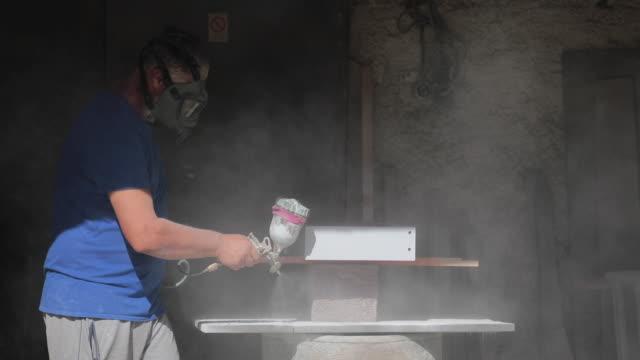 Man painting furniture with spay gun in carpenter workroom. Old furniture restoration business
