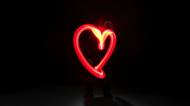 Man painting heart shape with light, stop motion