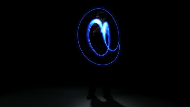 Man painting @ symbol with light