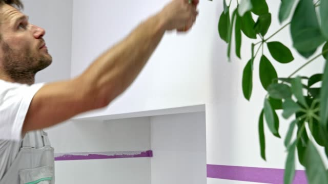 Man painting the wall white with a painting roller video