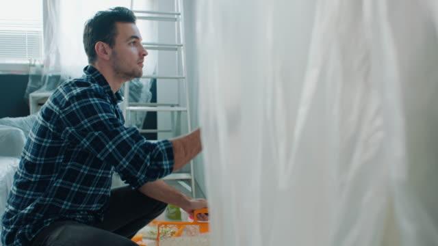 man målar vägg hemma - painting wall bildbanksvideor och videomaterial från bakom kulisserna
