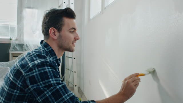 man painting wall at home - solo un uomo giovane video stock e b–roll