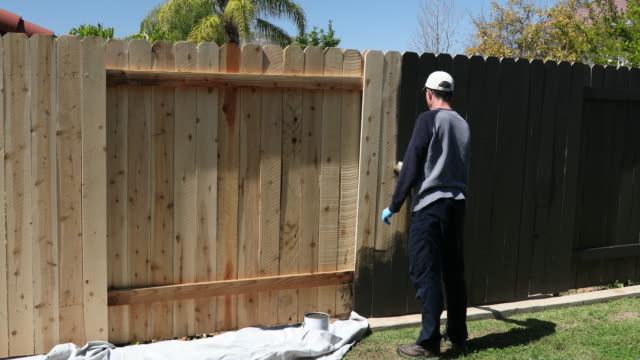 Man Paints Fence Hat and Gloves Wide Behind