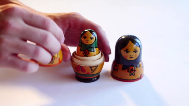 Man parses Matryoshka Doll on a white background in FullHD video