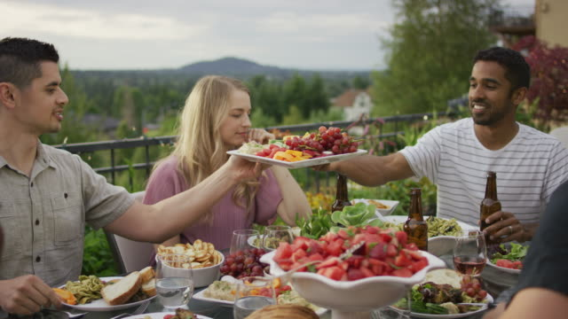 Man passes the fruit tray to his friend Young ethnic male passes a tray of fruit to his friend while at an outdoor dinner gathering barbecue meal stock videos & royalty-free footage