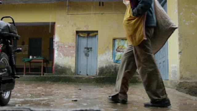 男性バックに雨の路地を通過します。 - 家系図点の映像素材/bロール