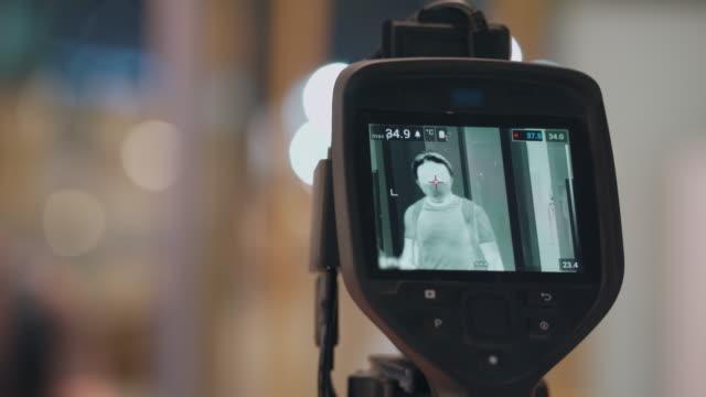体温をスキャンするために熱画像カメラを渡す男 - センサー点の映像素材/bロール
