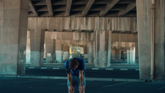 Man pauses jogging in urban setting video