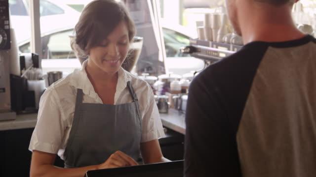 uomo che paga la bolletta del caffè usando tablet digitale girato su r3d - caffetteria video stock e b–roll