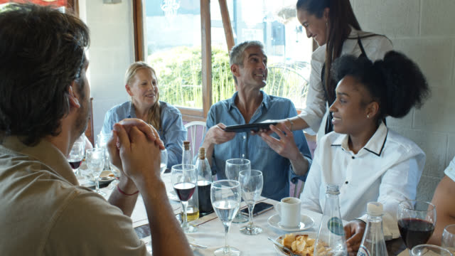 man paying check for delighted family at multi-generation gathering in argentinian parrilla restaurant - holiday and invoice family video stock e b–roll