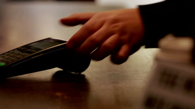 vídeos de stock e filmes b-roll de man paying with nfc technology on mobile phone, restaurant, shop - paying with card contactless