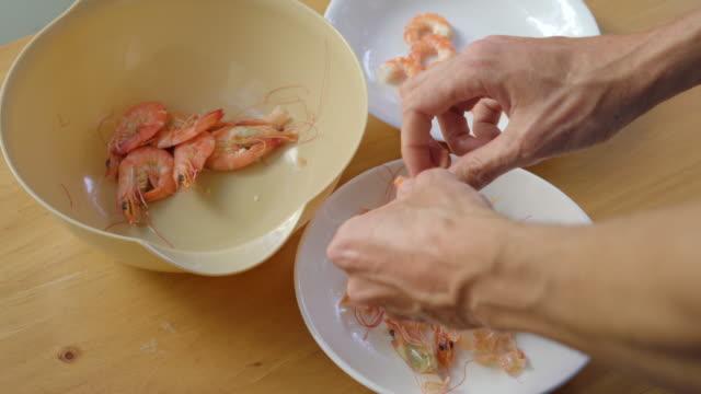 A man peels shrimps on a wooden table A man peels shrimps on a wooden table. peeled stock videos & royalty-free footage