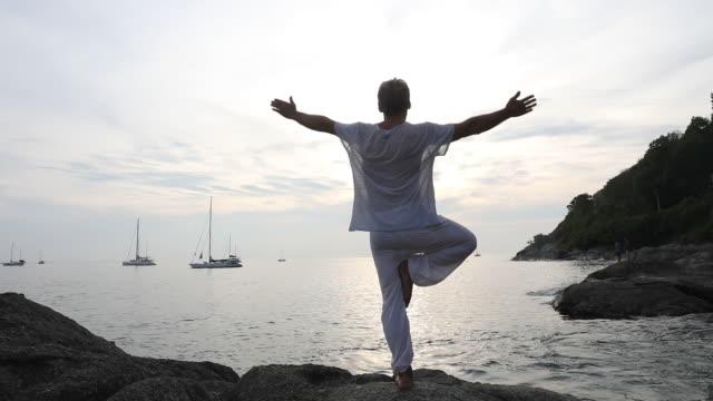 man utför yoga drag på kustnära rock platta - endast en man bildbanksvideor och videomaterial från bakom kulisserna