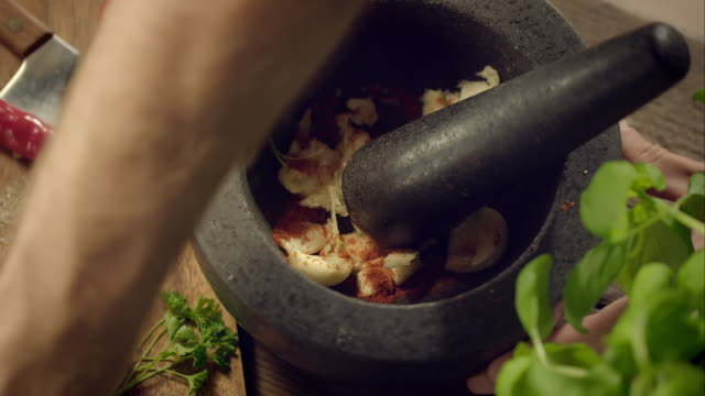 Man pestling garlic in a mortar Close-up shot of a man pestling garlic in a mortar. First he puts some spices in, then starts to pestle. mortar and pestle stock videos & royalty-free footage