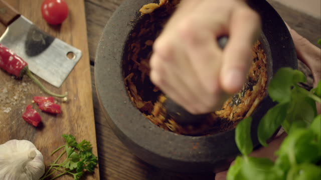 Man pestling garlic in a mortar Close-up shot of a man pestling garlic in a mortar. First he puts some spices in, then starts to pestle. When he's done, he removes the mortar from the table. mortar and pestle stock videos & royalty-free footage