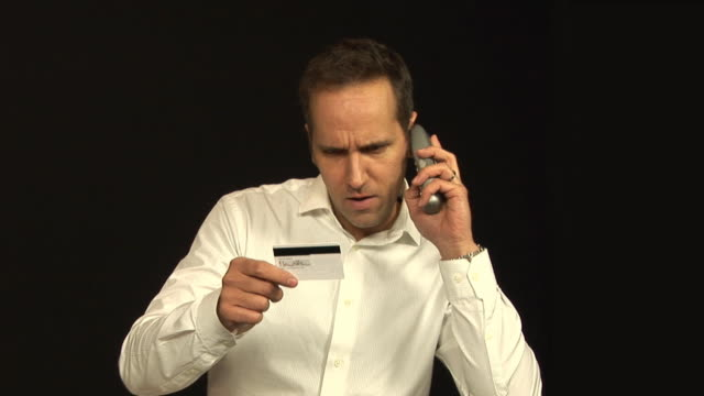 Man phone shopping with Credit card - HD & PAL Stock video clip footage of a man ordering goods over the phone with a credit card - Tripod cordless phone stock videos & royalty-free footage