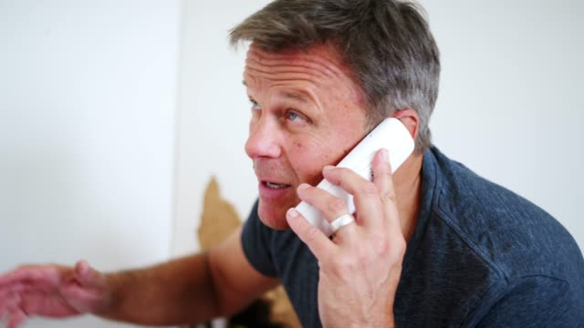 Man Phoning Emergency Plumber After Water Leak At Home