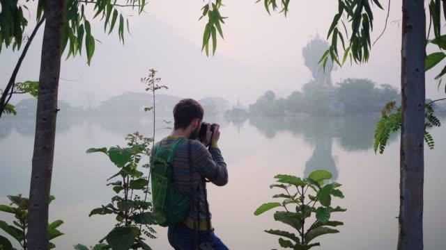 Man photographing Kyauk Kalat Pagoda on lake in Hpa-An