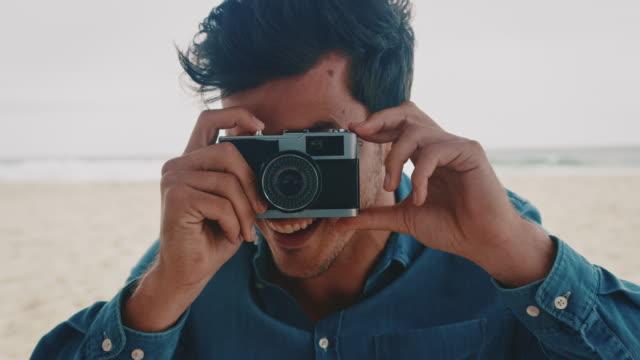 Man photographing through vintage camera at beach