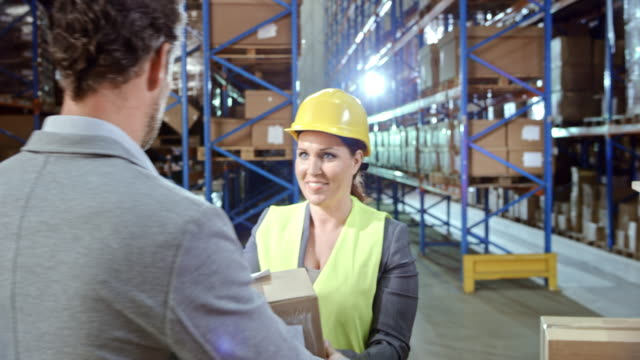 Man picking up a package in the warehouse video