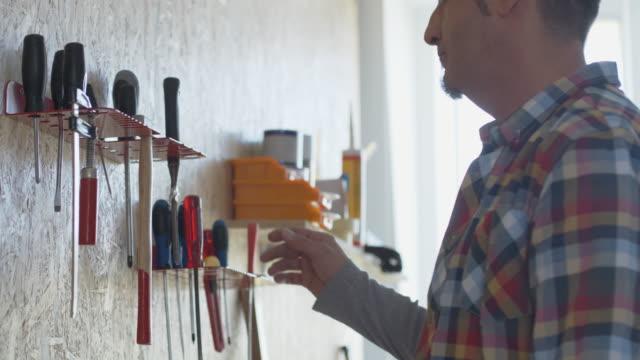 mann heben schraubenzieher von werkzeug-rack - garage stock-videos und b-roll-filmmaterial