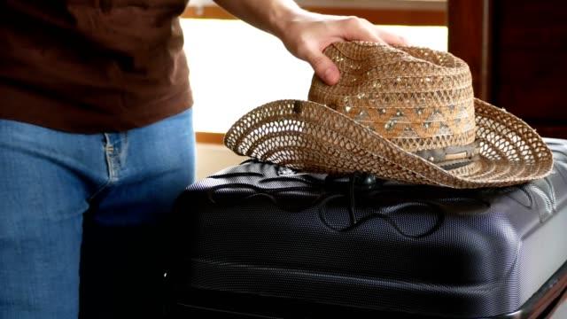 man hob strohhut und gepäck reisen aus schlafzimmer für unterwegs - strohhut stock-videos und b-roll-filmmaterial