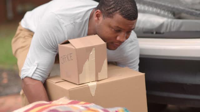vídeos de stock, filmes e b-roll de um homem pega três caixas móveis do chão e as leva para fora. - atividade física