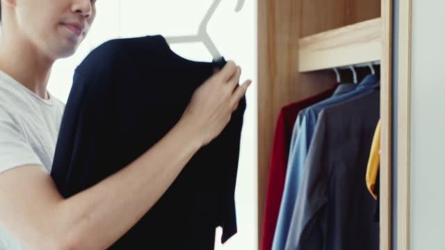 man picks up a black t-shirt from the wardrobe. - top nero video stock e b–roll