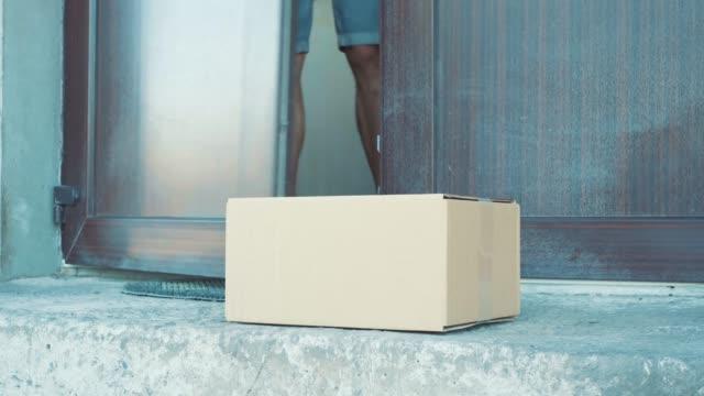 ein mann nimmt ein paket aus vor seiner haustür - schachtel stock-videos und b-roll-filmmaterial