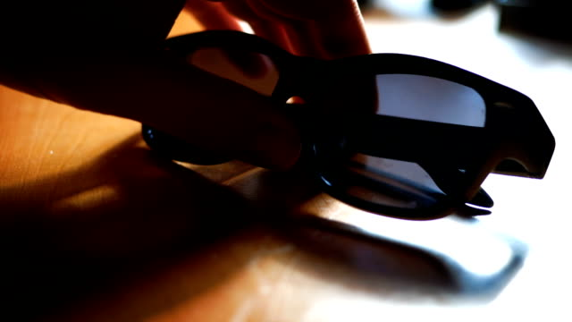Man picks up sunglasses off office table in summer Man picks up sunglasses off office table in summer gripping stock videos & royalty-free footage