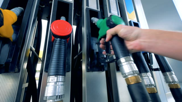 Man places a nozzle on a tank at a modern gas station. video