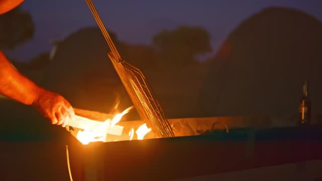 cu man barbekü ızgara altında kamp ateşine odun yerleştirerek - şömine odunu stok videoları ve detay görüntü çekimi
