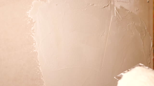 Man plastering wall in apartment