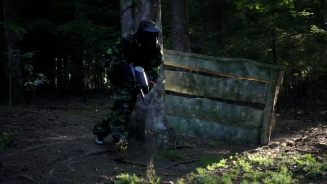Man player in paintball game with gun running on shooting range in forest video