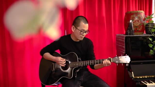 Man playing acoustic guitar and singing on a musical rehearsal