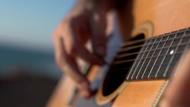 man spelar och tuning akustisk gitarr närbild shot sida vinkel skott utomhus - gitarrist bildbanksvideor och videomaterial från bakom kulisserna