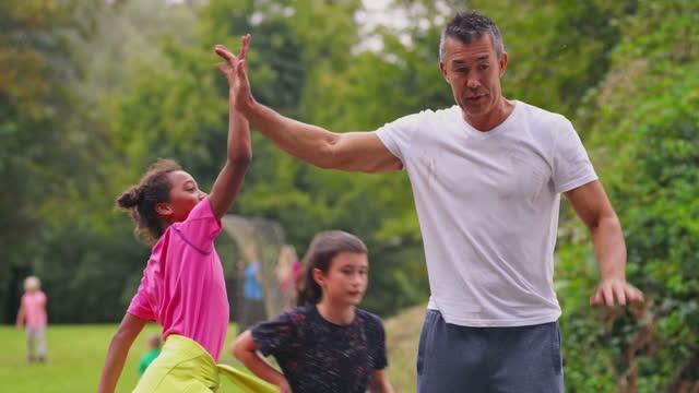 uomo che gioca a basket con i bambini e segna il tiro - immergere video stock e b–roll