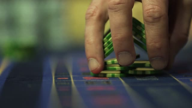 Man playing casino chips. Hand close-up