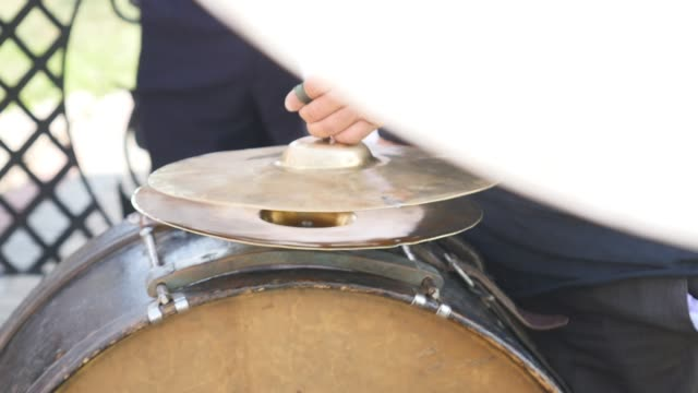 Man playing ceremony drum, close up video