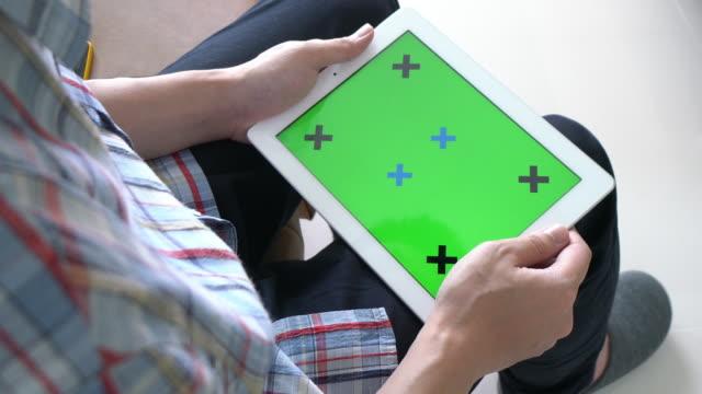 uomo che gioca a tablet digitale con schermo verde - insegna commerciale video stock e b–roll